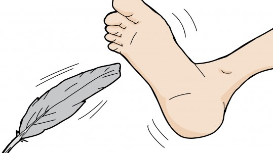 Gray feather tickling bottom of isolated foot